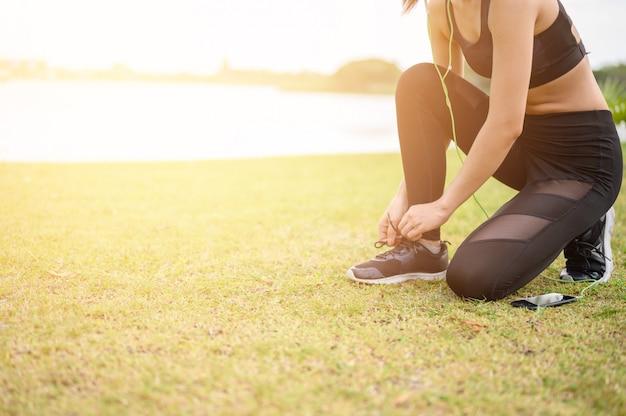 Vrouwelijke lopers zitten in een schoen riem klaar om te rennen.