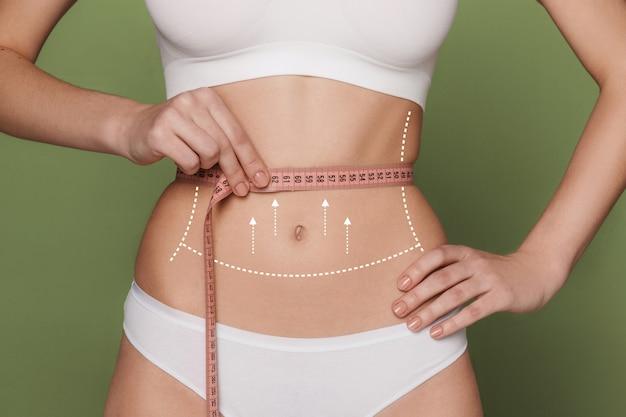 Vrouwelijke maag met een meetlint eromheen