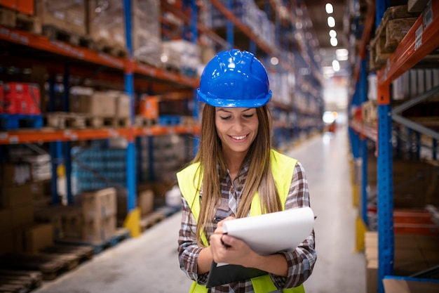 Vrouwelijke magazijnmedewerker controleren levering in grote distributie magazijn opslagruimte