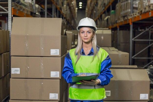 Vrouwelijke magazijnmedewerker die naar camera kijkt in logistiek centrum