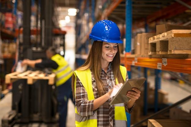 Vrouwelijke magazijnmedewerker die tablet controleert inventaris in distributiemagazijn