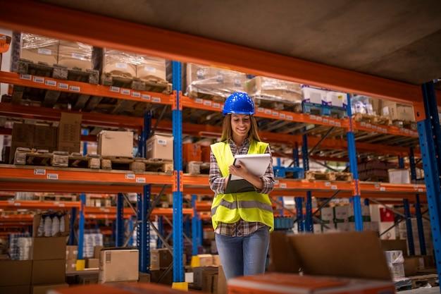 Vrouwelijke magazijnmedewerker inventaris in distributiemagazijn controleren