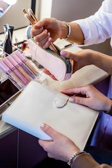 Vrouwelijke make-upartiest die een make-uptasje van het lesgeven aan de klant analyseert en penselen en lipgloss kiest