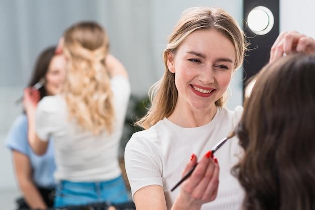 Vrouwelijke make-upkunstenaar die met model werkt