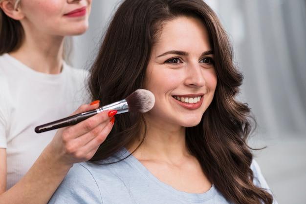 Vrouwelijke make-upkunstenaar die poeder toepassen