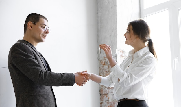 Vrouwelijke makelaar die een nieuw huis laat zien aan een jonge man na een discussie over huisplannen die een nieuw huisconcept verplaatsen