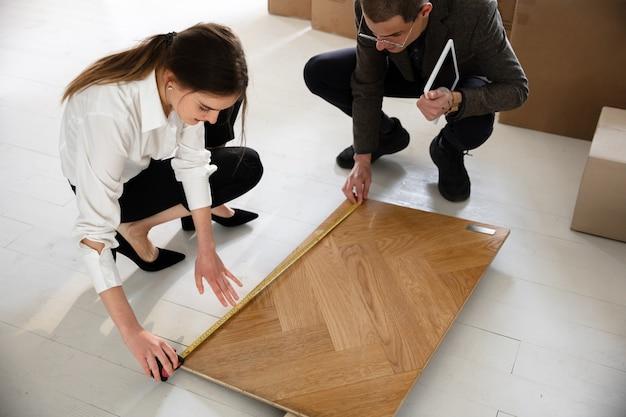 Vrouwelijke makelaar die nieuw huis toont aan een jonge mens na een bespreking over huisplannen, bewegend, nieuw huisconcept
