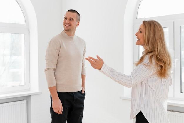 Vrouwelijke makelaar man nieuw huis tonen