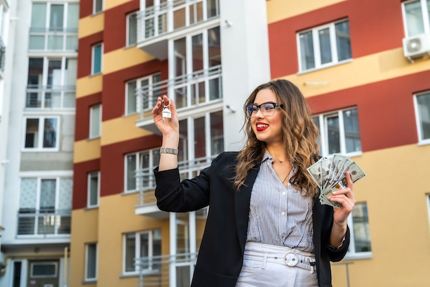 Vrouwelijke makelaar met sleutelhanger in de vorm van een klein huis en sleutels tegen huis als achtergrond