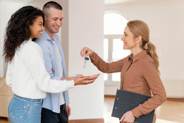 Vrouwelijke makelaar overhandigen paar de sleutels voor hun nieuwe huis