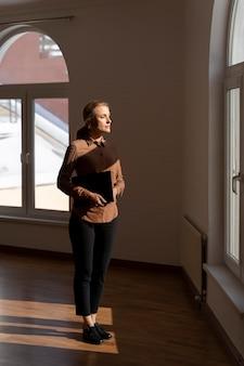 Vrouwelijke makelaar permanent in een leeg huis en kijkt door het raam