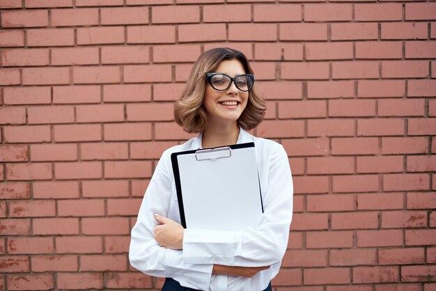 Vrouwelijke manager buitenshuis met documenten in de hand lichte achtergrond