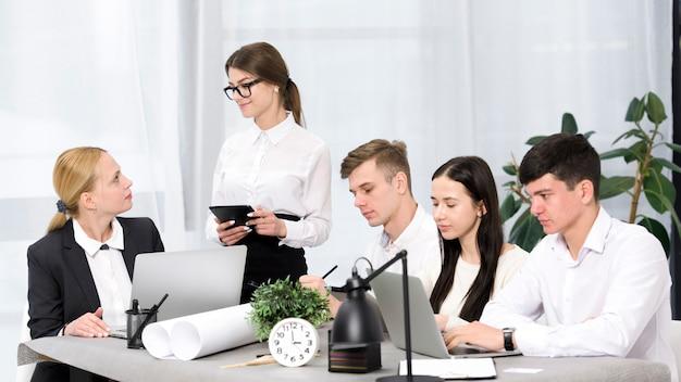 Vrouwelijke manager die het project met haar collega's in het bureau bespreekt