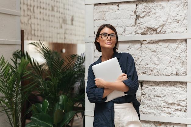 Vrouwelijke manager die in oogglazen omslag in handen houdt