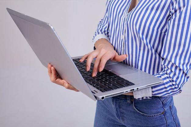 Vrouwelijke manager in een gestreept wit-blauw shirt met een laptop die zich op grijs bevindt. werknemer van het jaar, zakelijke dame. worker.