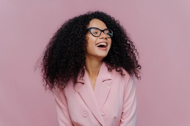 Vrouwelijke manager met een donkere huidskleur heeft kroeshaar, lacht van geluk