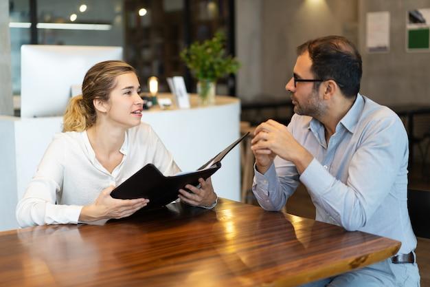 Vrouwelijke manager met omslag raadplegende collega