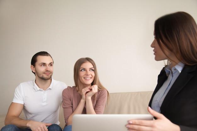 Vrouwelijke manager of makelaar in gesprek met jonge gelukkige paar binnenshuis