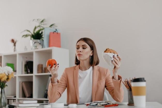 Vrouwelijke manager poseren in wit kantoor. dame kijkt met tegenzin naar appel en wil hamburger eten.
