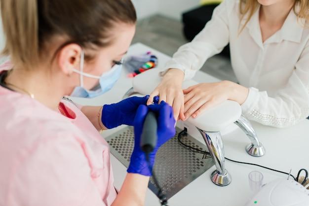 Vrouwelijke manicure meester in een schoonheidssalon werken met de handen van de klant