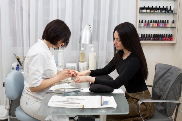Vrouwelijke manicure nagelriem schoonmaken met professionele manicure pusher tool