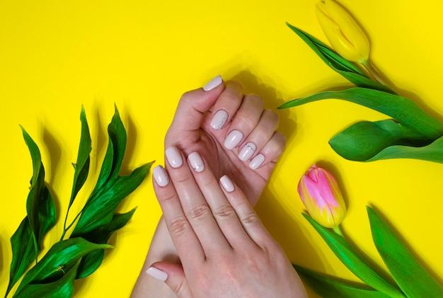 Vrouwelijke manicure op een lichte achtergrond. gele achtergrond met tulpen. banner.