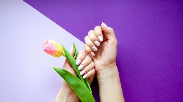 Vrouwelijke manicure op een lichte achtergrond. paarse achtergrond met bloemen. banner.