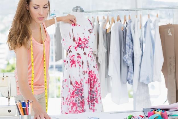 Vrouwelijke manierontwerper die aan bloemenkleding werkt
