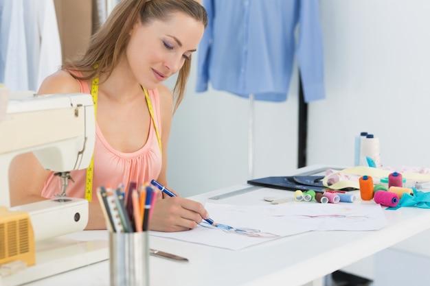 Vrouwelijke manierontwerper die aan haar ontwerpen werkt