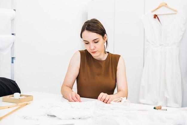 Vrouwelijke manierontwerper die aan kleding in studio werkt