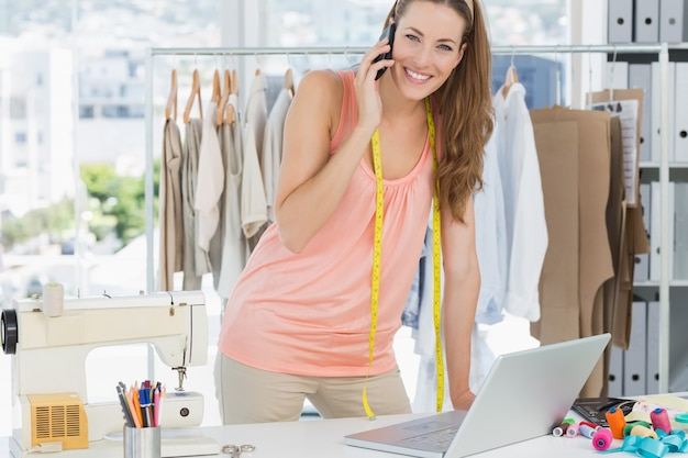 Vrouwelijke manierontwerper die laptop en cellphone in studio met behulp van