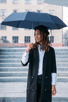 Vrouwelijke mannequin met een paraplu buitenshuis. humeurig weer. doordachte zwarte vrouw op regenachtige dag in selectieve focus, stijlconcept