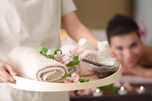 Vrouwelijke masseur bedrijf dienblad met spa therapie producten in wellness-centrum