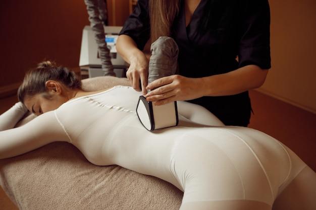 Vrouwelijke masseur met vibrerende stimulator en jonge vrouw in massagepak ontspannen op tafel. massage en ontspanning, lichaams- en huidverzorging. aantrekkelijke dame liggend in spa salon