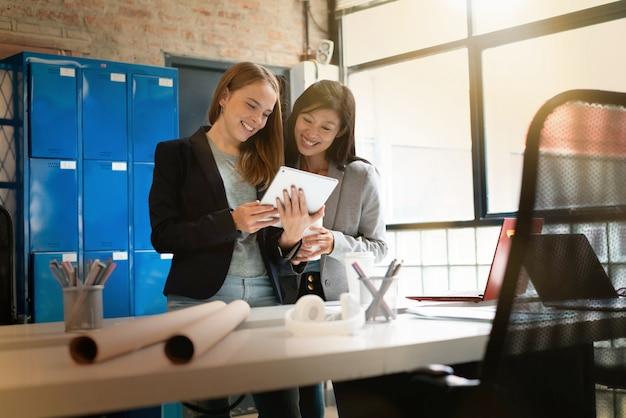 Vrouwelijke medewerkers die presentatieideeën bespreken in modern bureau
