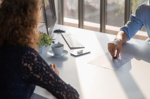 Vrouwelijke medewerkers staan op het punt een contract te tekenen om te werken op het hoofd van de personeelsafdeling op het kantoor.
