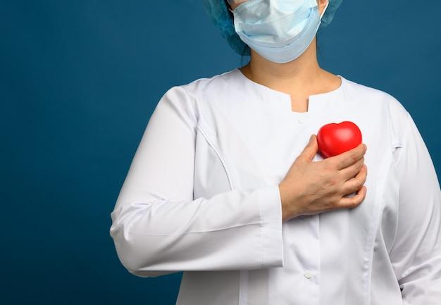 Vrouwelijke medic in een witte jas, een masker staat en houdt een rood hart op een blauwe achtergrond, het concept van donatie en vriendelijkheid