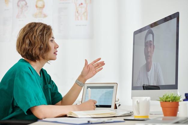 Vrouwelijke medische werker in gesprek met zieke patiënt en zijn klachten opschrijven