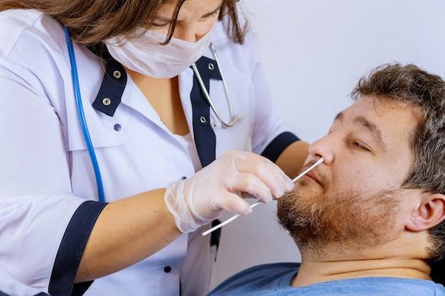 Vrouwelijke medische werker neemt een uitstrijkje voor coronavirus-monstertest van een mogelijk geïnfecteerde man met chirurgische gezichtsmaskers personeel neemt een neusmonster