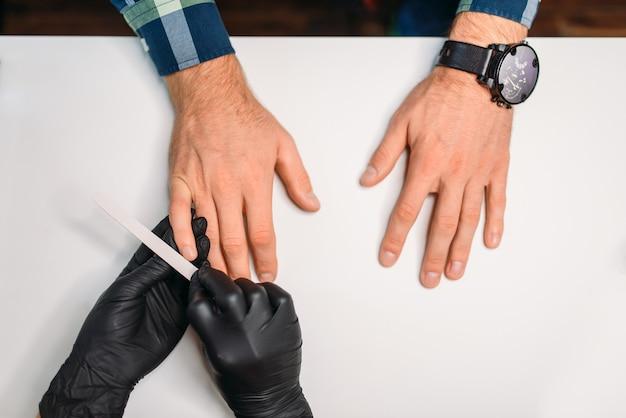 Vrouwelijke meester in zwarte handschoenen nagels polijsten aan mannelijke klant, bovenaanzicht