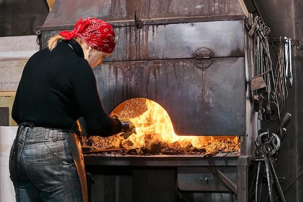 Vrouwelijke metaalkunstenaar verwarmt een werkstuk in een brandende smederij