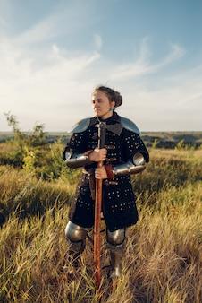 Vrouwelijke middeleeuwse ridder poseert in harnas tegenover het kasteel, geweldig toernooi. gepantserde oude krijgers in harnas poseren in het veld