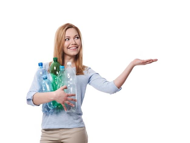 Vrouwelijke milieuactivist met plastic flessen die op exemplaarruimte tonen