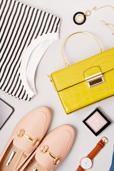 Vrouwelijke mode-accessoires, schoenen, shirt, make-up en handtas.