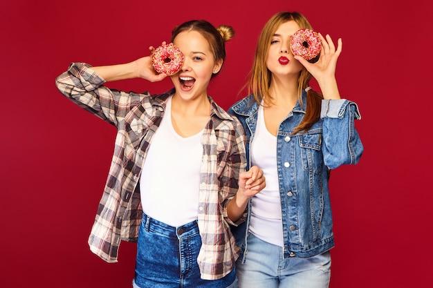 Vrouwelijke modellen die roze donuts houden met bestrooit