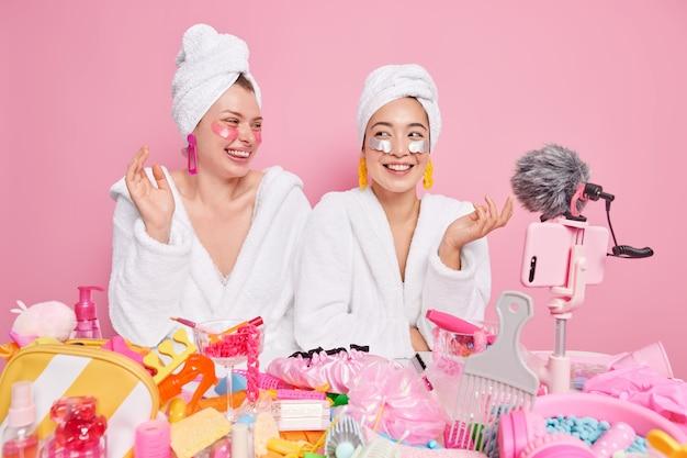 Vrouwelijke modellen glimlachen breed ondergaan schoonheidsbehandelingen aanbrengen patches onder de ogen video opnemen via smartphone poseren tegen roze