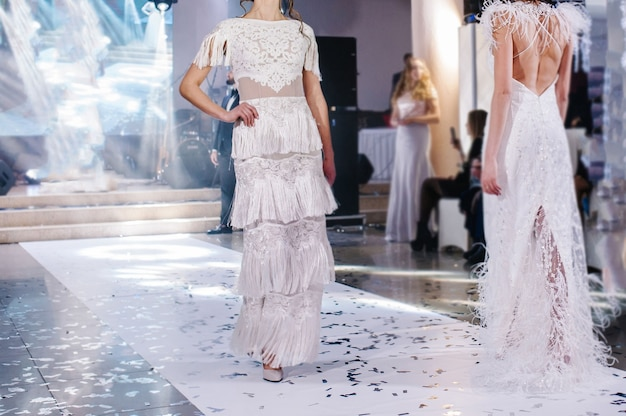 Vrouwelijke modellen lopen over de landingsbaan in prachtige stijlvolle witte trouwjurken