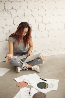 Vrouwelijke modeontwerper bezig met een laptop in haar studio controleren stoffen en schetsen zittend op de vloer. creatieve industrie.