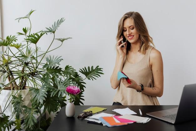 Vrouwelijke modeontwerper die aan de telefoon praat met haar klant