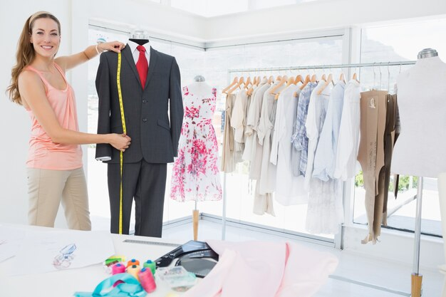 Vrouwelijke modeontwerper maatpak op dummy
